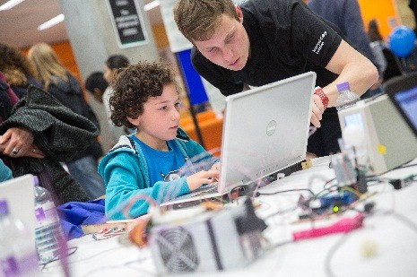 A young student receives guidance at a maker event at Imperial College London.