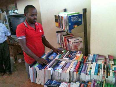 "Musyoki Nzambu, a Clinical Officer at Mwingi District Hospital in Kenya, with the new donated books: ""I am very impressed. I have not seen some of the titles even in my college library,"" he said. He added that he would introduce the library team to the Mwingi district hospital so that they could promote the information health resources in the library."