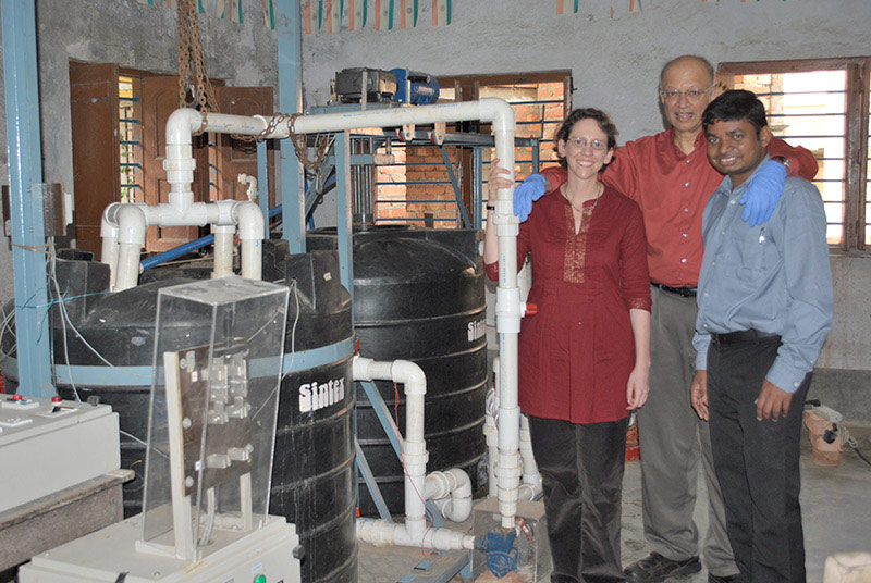 The Electrochemical Arsenic Remediation (ECAR) research team with their water treatment prototype in Kolkata, India in 2012. This photo is from a pilot installation of an arsenic removal reactor, deployed at a high school near Kolkata.  Prof. Ashok Gadgil, Science and Technology Deputy for Energy Technologies at the Lawrence Berkeley National Laboratory (center), poses with Dr. Susan Amrose, a scientist at UC Berkeley, and Siva Bandaru, then a local engineer hired by the ECAR project to work In India. Siva became a collaborator with the Berkeley research team, co-authoring publications as part of this work. He was admitted to UC Berkeley as a PhD student in the Civil and Environmental Engineering Department in 2014, and remains involved in the original ECAR project from the research side. (Photo: Gadgil Lab for Energy and Water Research).