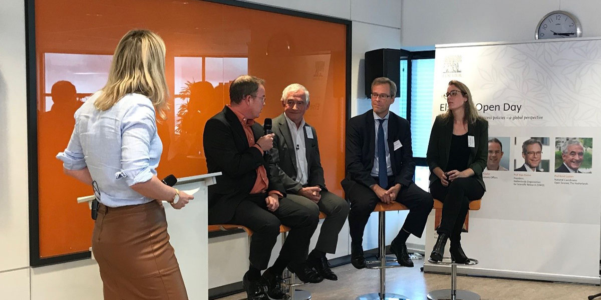 Panelists talk about open access at Elsevier's Amsterdam office: Dr. Nick Fowler, Chief Academic Officer at Elsevier; Prof. Karel Luyben, National Coordinator for Open Science (the Netherlands); Prof. Stan Gielen, President of the Netherlands Organisation for Scientific Research (NWO); and Dr. Barbara Braams, Assistant Professor at Vrije Universiteit Amsterdam. The moderator is Charlotte Geerdink, founder of Charly Speaks.