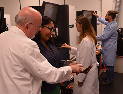 Dr. Chris Barker of NC TraCS and Dr. Sharlini Sankaran of REACH NC collaborate at the UNC High-Throughput Gene Sequencing Facility.
