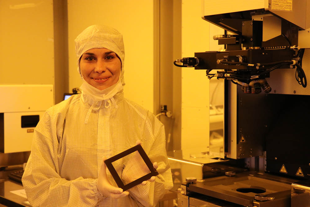 In the Clean Room Lab at NYU Abu Dhabi, Ghada holds a mask she printed using Heidelberg mask writer DWL to fabricate devices based on various 2D materials and heterostructures to understand their opto-electronic properties. She is working on a photolithography machine wearing the required PPE.