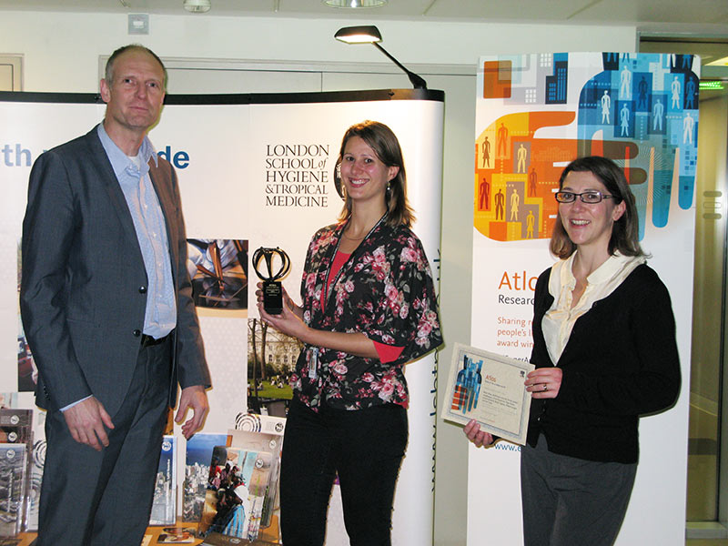 Dr. Floris de Hon, Publishing Director for Life Sciences at Elsevier, and Zoe Mullan, Editor of <em>The Lancet Global Health</em>, present the first Atlas Award to Dr. Katie Greenland, Research Fellow at the London School of Hygiene and Tropical Medicine (center), for her article &quot;SuperAmma to the hand washing rescue.&quot; &quot;We're honored to be able to raise the profile of this work,&quot; Dr. Greenland said. &quot;The award is especially poignant for us because a key member of our team, Kiruba Sankar, tragically died recently. We're pleased to be able to publically recognise his work.&quot;