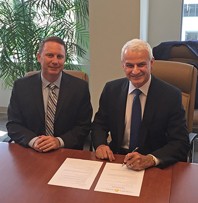 Elsevier CEO Ron Mobed (right) and M. Matthew Owens, VP for Federal Relations and Administration at the Association of American Universities and a member of the Golden Goose Award's steering committee, sign the agreement for Elsevier's commitment of $250,000 for the award.
