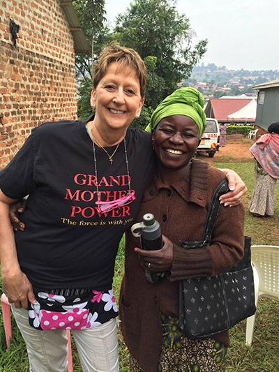 Cindy Tryniszewski, RN, MSN, with a member of the Grandmother Power project in Uganda, which educates grandmothers to provide health guidance for their grandchildren. It's one of many Project Helping Hands initiatives around the world.