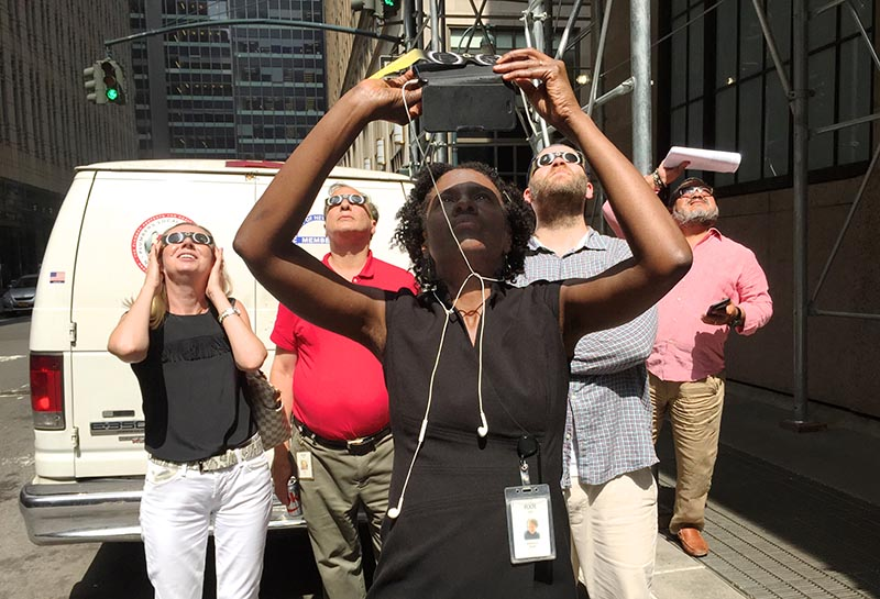 Angelica Kerr photographs eclipse as her colleagues watch with eclipse glasses (left to right): Liz Perill, Executive Publisher; Allan Ross, Senior Publisher, Health and Medical Science Journals; and Michael Weston.