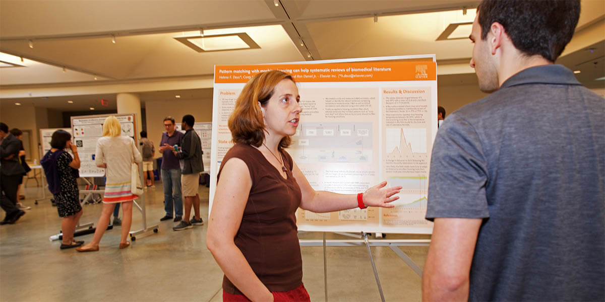 Helena Deus, PhD, a Technology Research Director at Elsevier, presents her research team's poster at the Harvard Postdoc Research Symposium this spring. (Photo by Alison Bert)