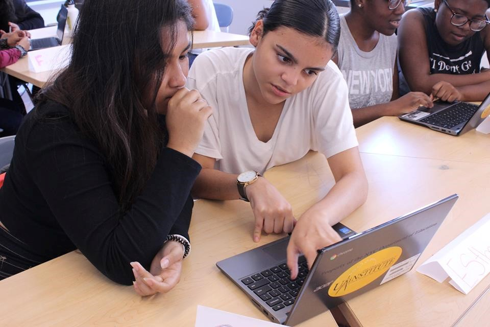 Maryrose and Ester analyze data after compiling it from a database on out-of-school suspension rates in America. (Credit: Girls Inc. of New York City, copyright 2018).