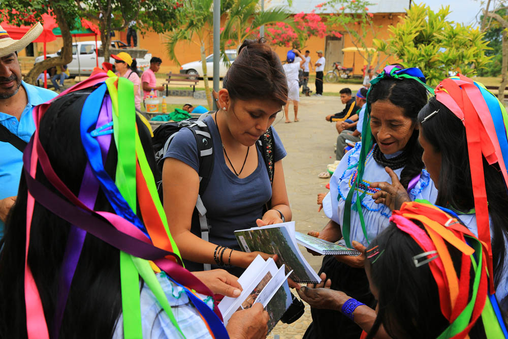 Dr. Narel Paniagua-Zambrana in the Lamas community in Northern Peru, giving out books documenting the knowledge of the Chankas, an indigenous group she worked with to document their use of palms and return the knowledge to the community (Photo by Rainer Bussmann).