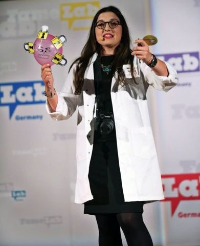 Karina Pombo-García performing in the finals at FameLab Germany 2014. In her 3-minute talk, she illustrated how nanoparticles reach cancer cells to diagnose tumors in patients.