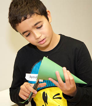 Ayoub Aakouk, 11, constructs a bottle rocket in astronomy class.