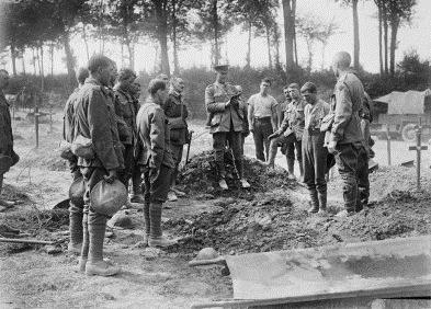 France, August 1916: Picardie, Somme, Albert, Becourt Wood – A chaplain reads the burial service beside the grave of a fallen Australian in a cemetery in a wood, near a chateau that housed a casualty clearing station. (Australian War Memorial Collection EZ0064).