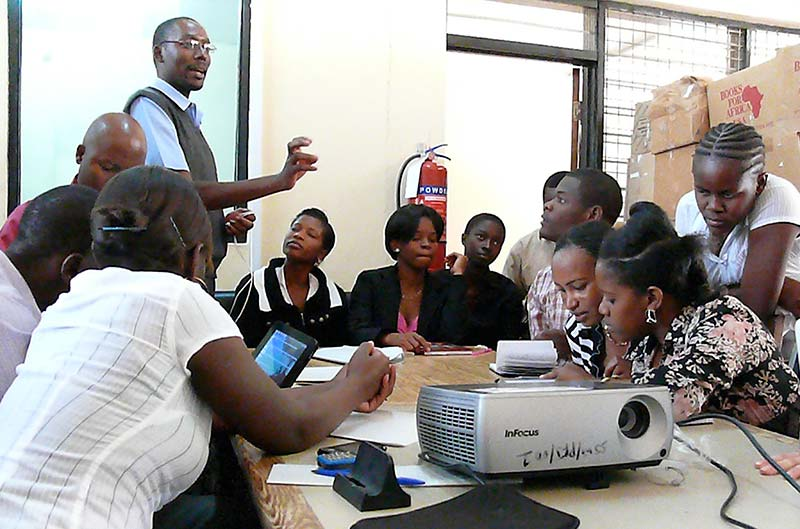 <strong>Library e-resources training.</strong> Martin Kusekwa, Librarian at St. John's University of Tanzania in Dodoma, is training library staff on the use of e-resources, demonstrating the library's newly acquired e-readers for students and staff. Liesbeth Kanis helped Kusekwa prepare the workshop and get funding to aquire the e-readers. (Copyright &copy; Floris Janssens-Andrejew)