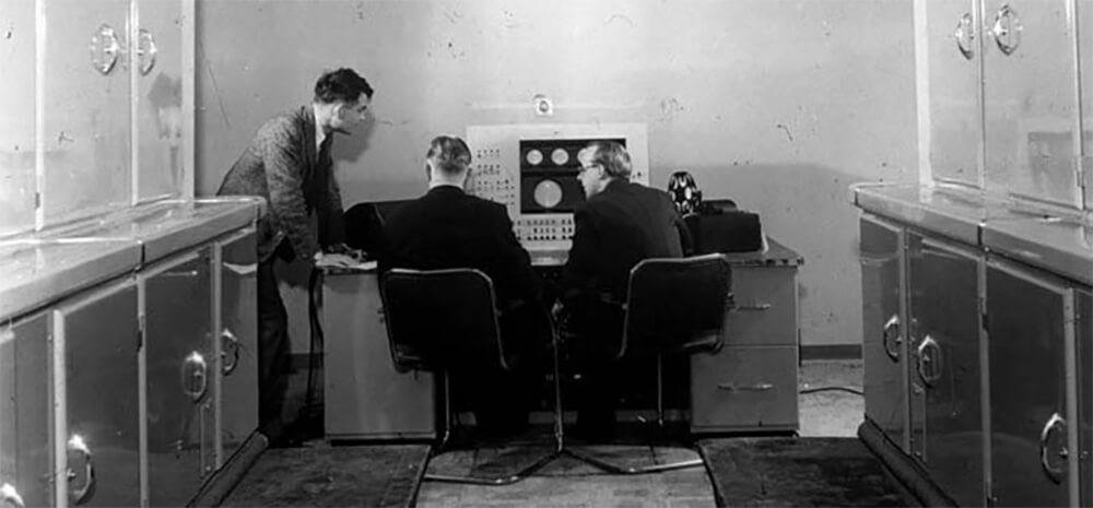 Alan Turing – founding father of electronica? Yes, add that to his credentials as computer science mastermind and codebreaker. (In this photo, ca. 1951, he's at the console of the Manchester Mark I computer, from <em>Alan Turing: His Work and Impact</em>, Elsevier, 2013)