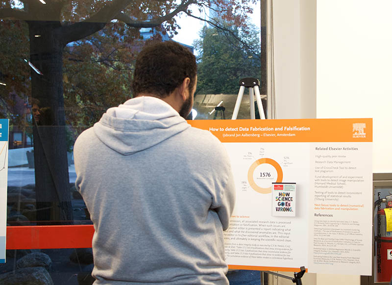 "A Harvard student studies the poster on ""Research Integrity:  How to Detect Data Fabrication and Falsification"" by Dr. IJsbrand Jan Aalbersberg, SVP of Research Integrity at Elsevier, presented by Cell Press CEO Dr. Emilie Marcus. (Photo by Alison Bert)"