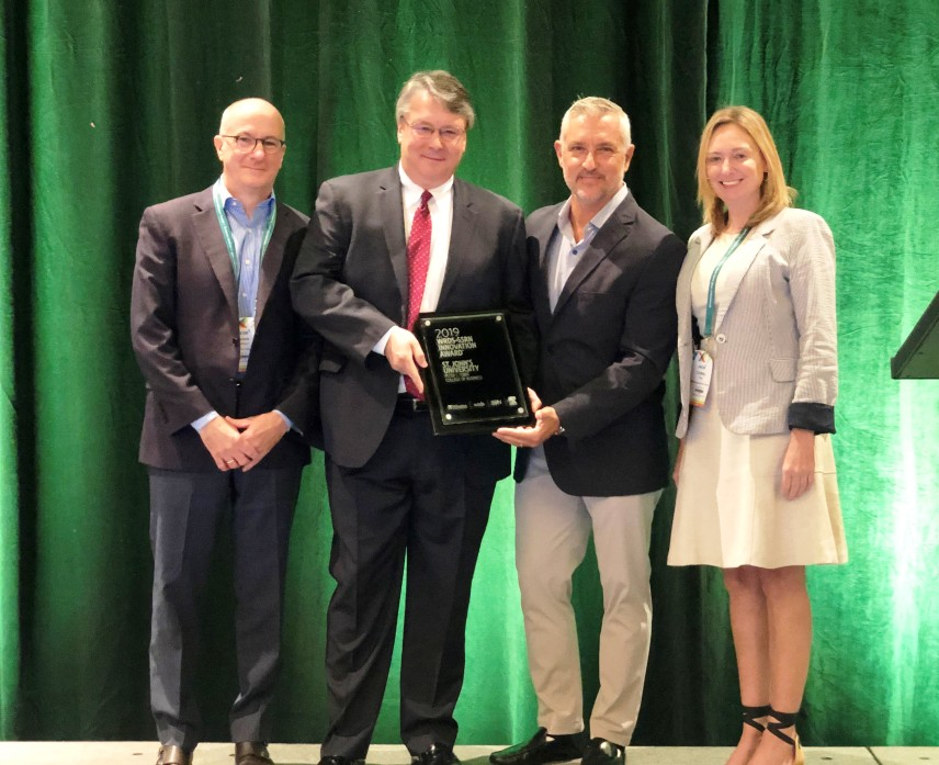 Image of Award Presentation including winner from St. John's University's Peter J. Tobin College of Business and reprsentatives of SSRN and WRDS