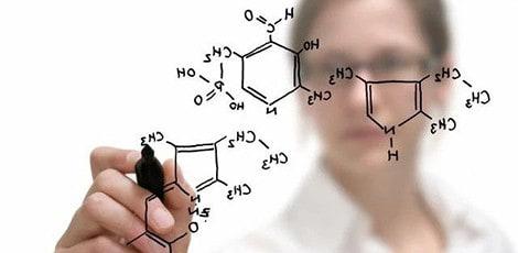 Chemist writing formula on glass board