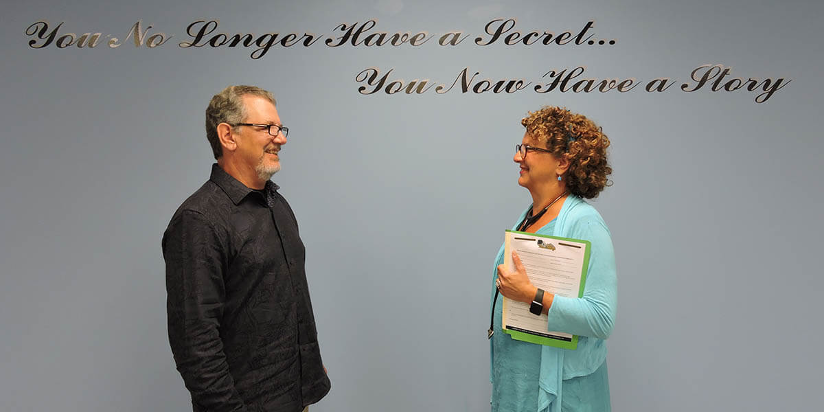 Physicians Leslie Dye, MD, and Bradley R. Wolf, MD, under an inspirational sign in the lobby of <a target=