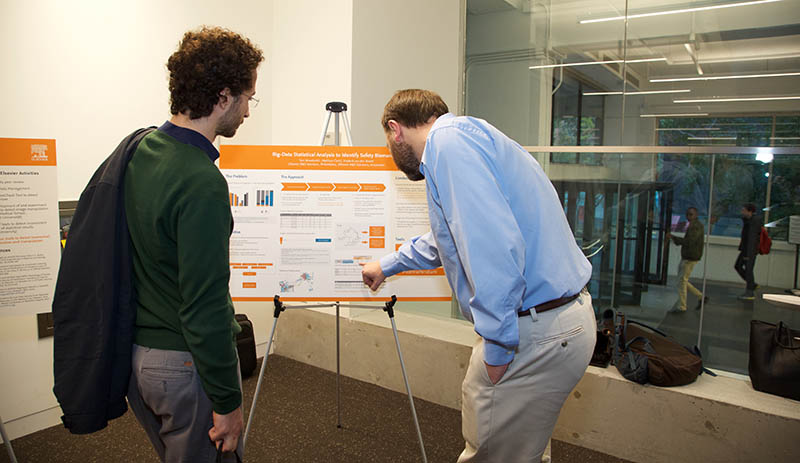 "Dr. Thomas Woodcock, a data scientist for Elsevier's Professional Services team, talks about his poster with a medical student: ""Big-Data Statistical Analysis to Identify Safety Biomarkers."" (Photo by Alison Bert)"