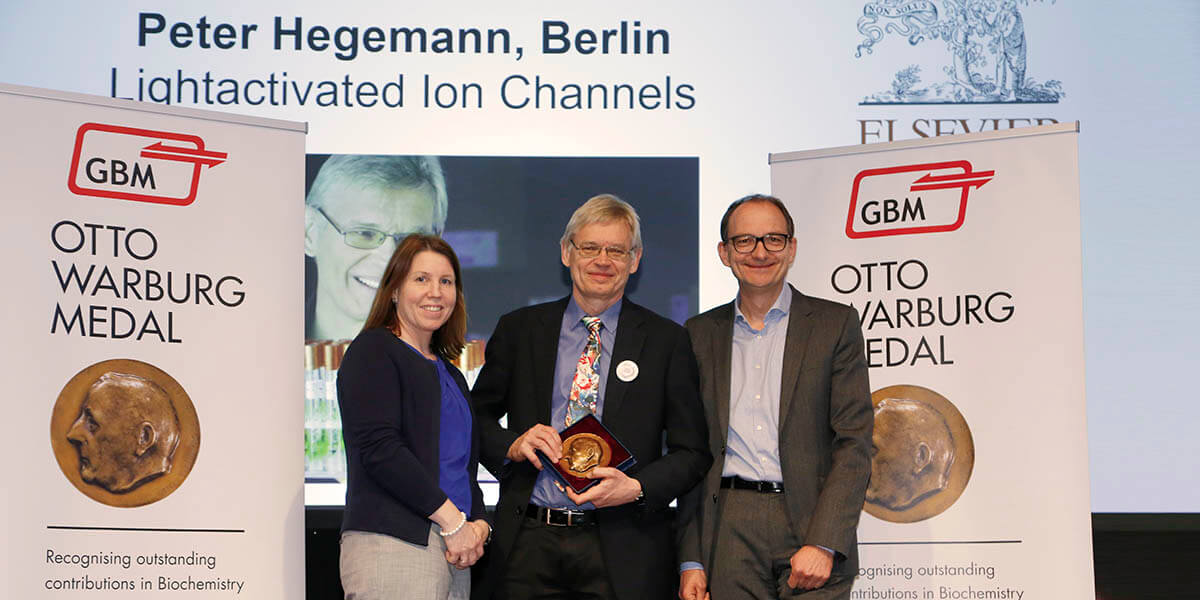 Otto Warburg Medal awardee Prof. Peter Hegemann (center) with GBM President Prof. Johannes Herrmann (right) and Elsevier Publishing Director Andrea O'Brien (left).