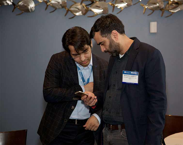 Dr. Yasin Ozcan, a Postdoctoral Fellow at Sloan School of Management, MIT (right) chats with Dr. Bhaven Sampat, Associate Professor in the Department of Health Policy and Management at Columbia University. (Photo by Alison Bert)
