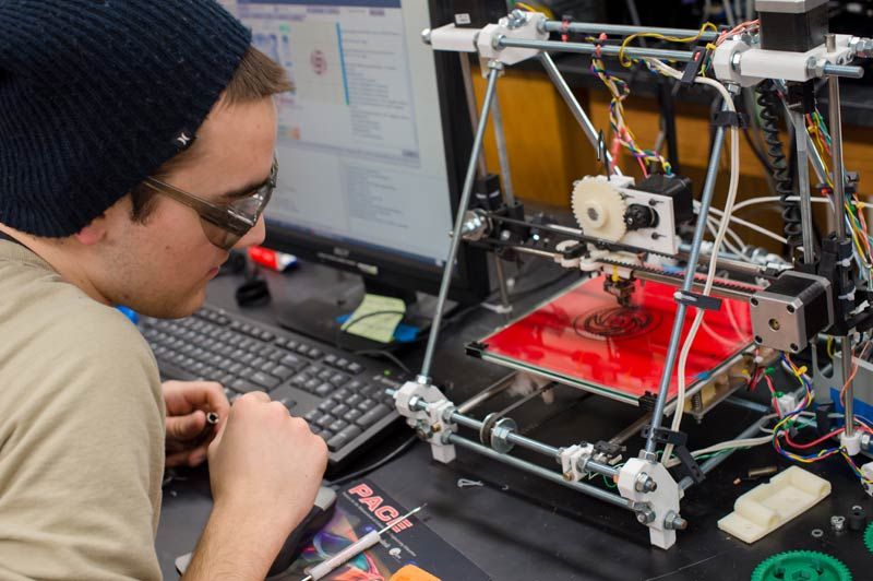 Student John Laureto working with a third-generation Mendel Prusa RepRap 3D printer. This printer uses even fewer parts and is easier to assemble and maintain. (Photo by Susan Bird)