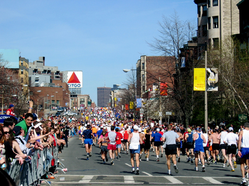 Runners in the Boston Marathon on Beacon Street coming into Kenmore Square (Photo by Noah Reid)