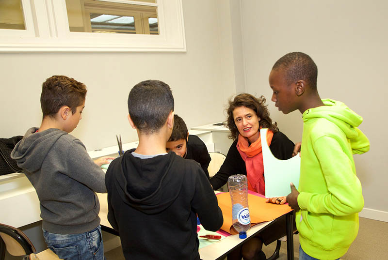 Heleen Terwijn, a psychologist who founded the Weekend School, helps students build bottle rockets for the astronomy lesson.