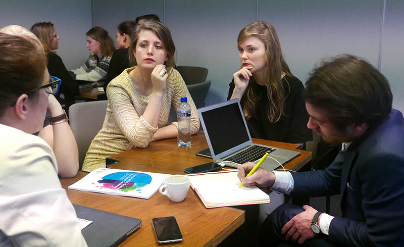 Students at AIESEC's YouthSpeak Forum work on projects to communicate about sustainability initiatives at Elsevier.