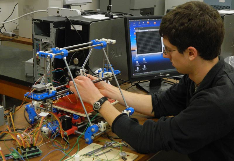 Graduate student Brennan Tymrak working on a second-generation Mendel RepRap 3D printer.