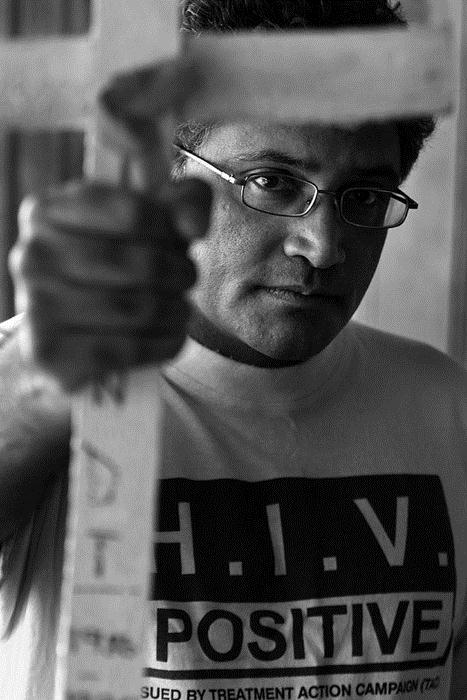 Activist Zackie Achmat displays a white cross at his home in Cape Town. The cross is a used by the Treatment Action Campaign during protests and is marked with the name of an HIV victim. (Photo by Joao Silva; Image courtesy of UCT Special Collections)