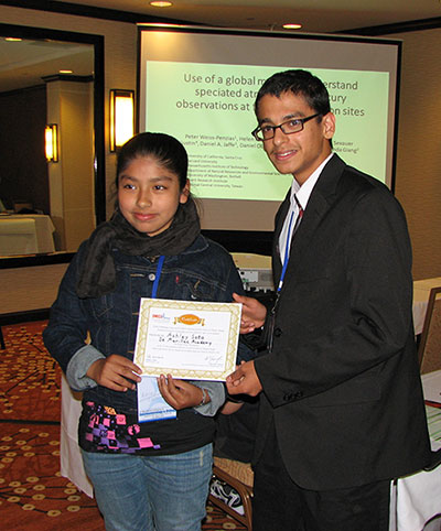 Suganth Kannan presents a certificate to Ashley Soto of De Marillac Academy in San Francisco, winner of the middle school Poster Competition he organized in conjunction with the conference.