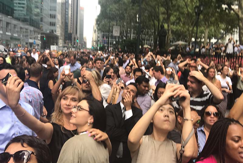 In contrast to the Elsevierians, the crowds outside Bryant Park were less scientific in their viewing – no eclipse glasses, staring at the sun and taking selfies. (Photo by Tom Reller)