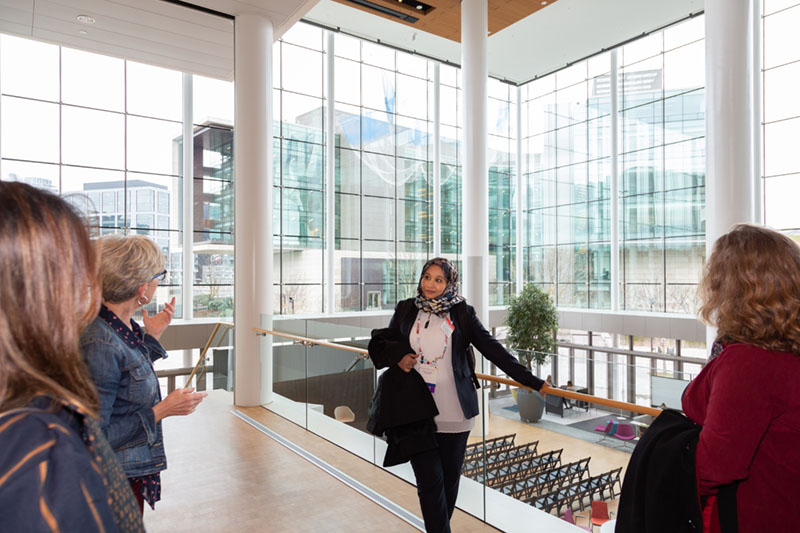 "In the atrium overlooking the ""living room"" of the Gates Foundation. Fathiah Zakham, PhD, Assistant Researcher and Lecturer at Hodeidah University in Yemen and winner of a 2020 OWSD-Elsevier Foundation Award, talks with our tour guide, Debra Burke, Project Coordinator for the Gates Foundation finance team. (Photo by Alison Bert)"