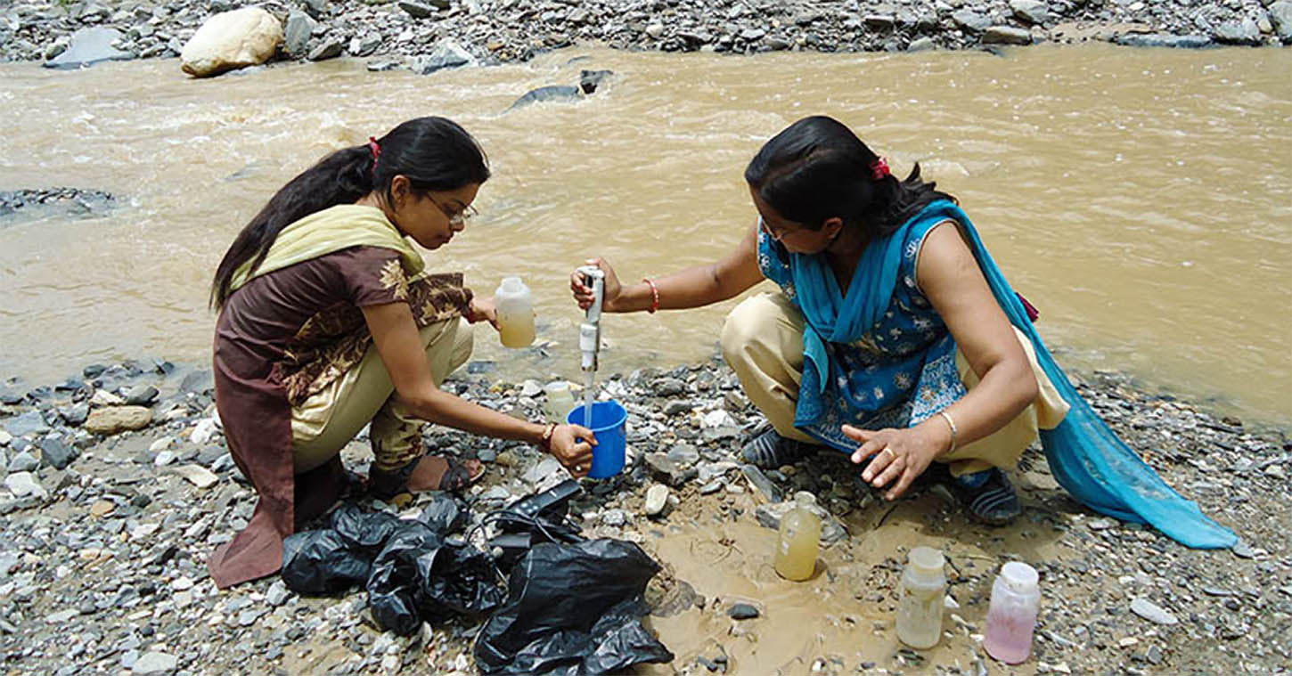 As a researcher at the Nepal Academy of Science and Technology (NAST), Dr. Tista Prasai Joshi (right), collects a river water sample with Research Assistant Lerensa Shrestha in the Nuwakot District, near Kathmandu. They are monitoring water pollution. (Photo by Mahesh Kafle)