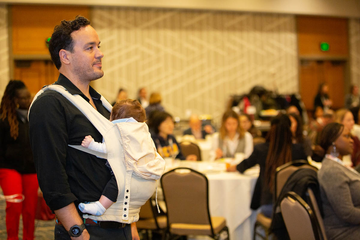 Dr. Jalel Sager, the husband of Dr. Susana Arrechea, watches the ceremony with their 4-month-old daugher, Aya. (Photo by Alison Bert)