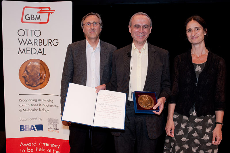 Prof. Nikolaus Pfanner, PhD, (center) displays the Otto Warburg Medal at the award ceremony, with Prof. Johannes Buchner, PhD, President of GBM, and Dolors Alsina Vila, Executive Publisher of <em> BBA – Biochemica et Biophysica Acta.</em> at Elsevier.