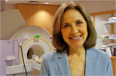 Helen Fisher, PhD, with the fMRI scanner she uses for her brain scanning experiments (Photo by Christian Frei)