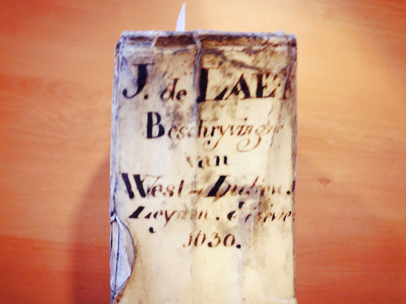 Worn vellum cover of History of the New World, Second Edition, with hand-scribed information on the spine