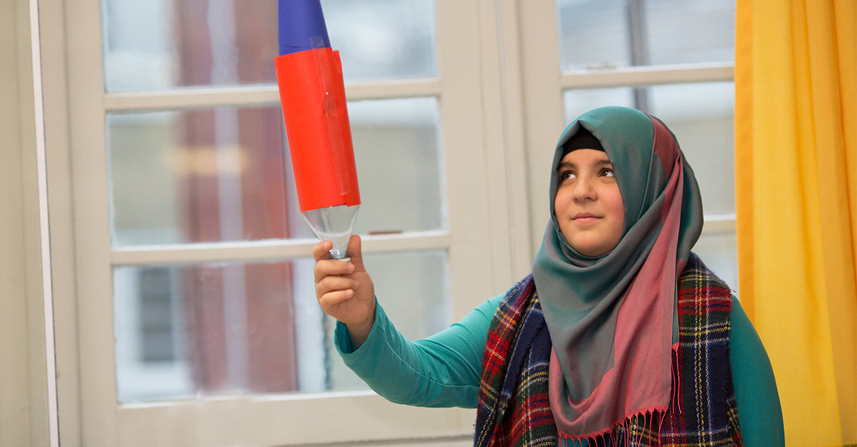 Nazli Kocyigit, a student at the IMC Weekend School, displays the bottle rocket she made in astronomy class. (Photography by Alison Bert)