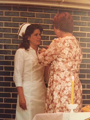 Cherie receives her pin and cap as she graduates from nursing school. Now she helps others fulfill that dream.