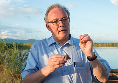 Prof. Marcel Tanner, PhD,  Editor-in-Chief of <em>Parasite Epidemiology and Control</em>,  explains bilharzia disease at Kilombero river in Tanzania. (Credit: Christian Heuss, 2015)