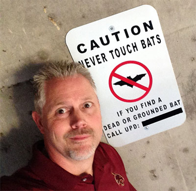 Prof. Rodney E. Rohde poses near a sign that was put up immediately after a harrowing ordeal on campus.