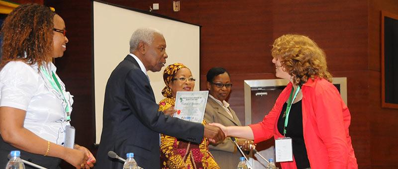 Ylann Schemm shakes hands with Dr. Seif Seleman Rashid, the Tanzanian Minister for Health and Social Welfare, accepting thanks for the Elsevier Foundation's support of the 2014 Association of African Health Libraries conference, as AHILA President Nasra Gathoni (far left) looks on. Ylann worked with eight Foundation projects to present a panel discussion at AHILA exploring best practices in mapping health information to outcomes.