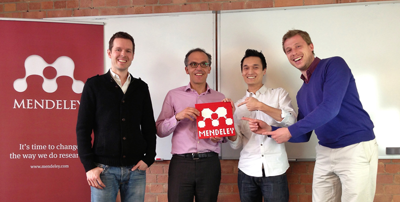 Olivier Dumon, now Chief Product Officer at Elsevier (holding sign), with Mendeley founders (left to right) Paul Foeckler, Dr. Victor Henning and Jan Reichelt in 2013.