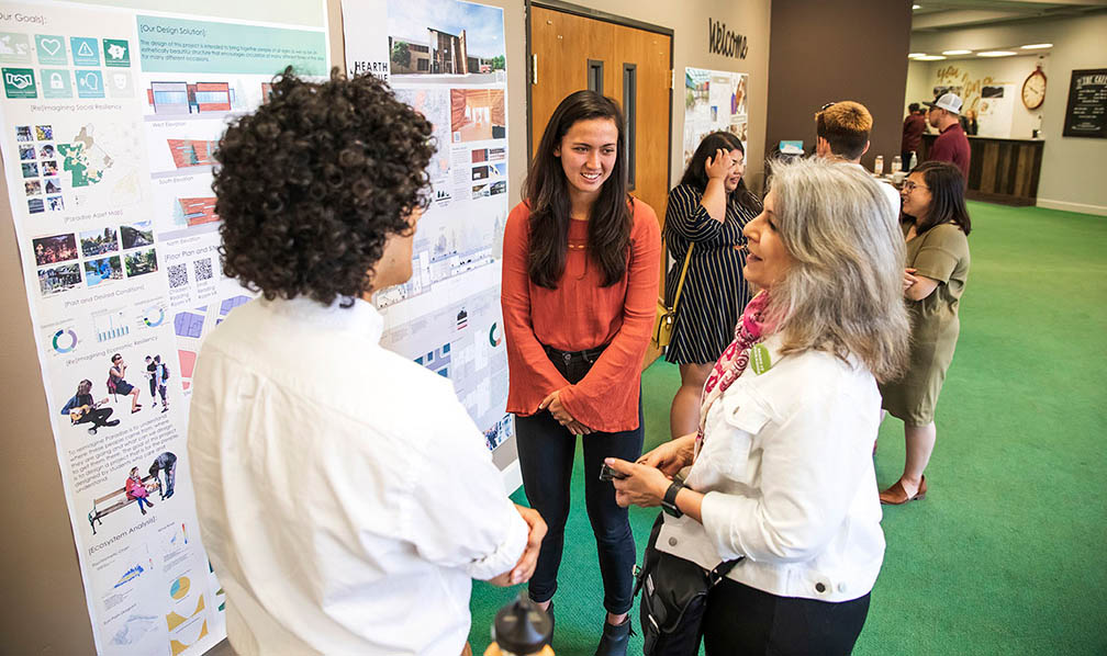 Paradise Town Council member Melissa-Schuster talks with students Alessandro Zanghi and Zoey Fox about their designs. (Photo by Joe Johnston/Cal Poly)