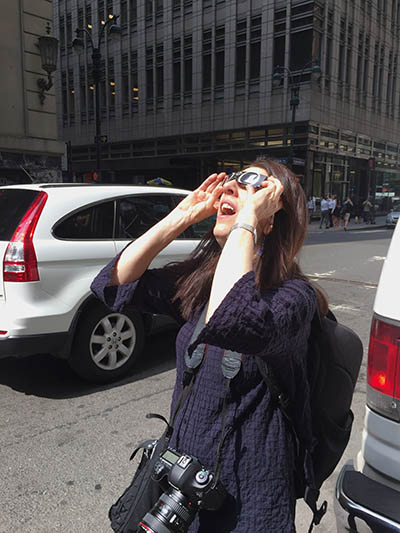 Alison Bert watches the eclipse in New York City. (Photo by Liz Perill)